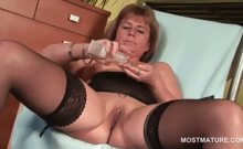 Mature lady in stockings fingering her starved snatch